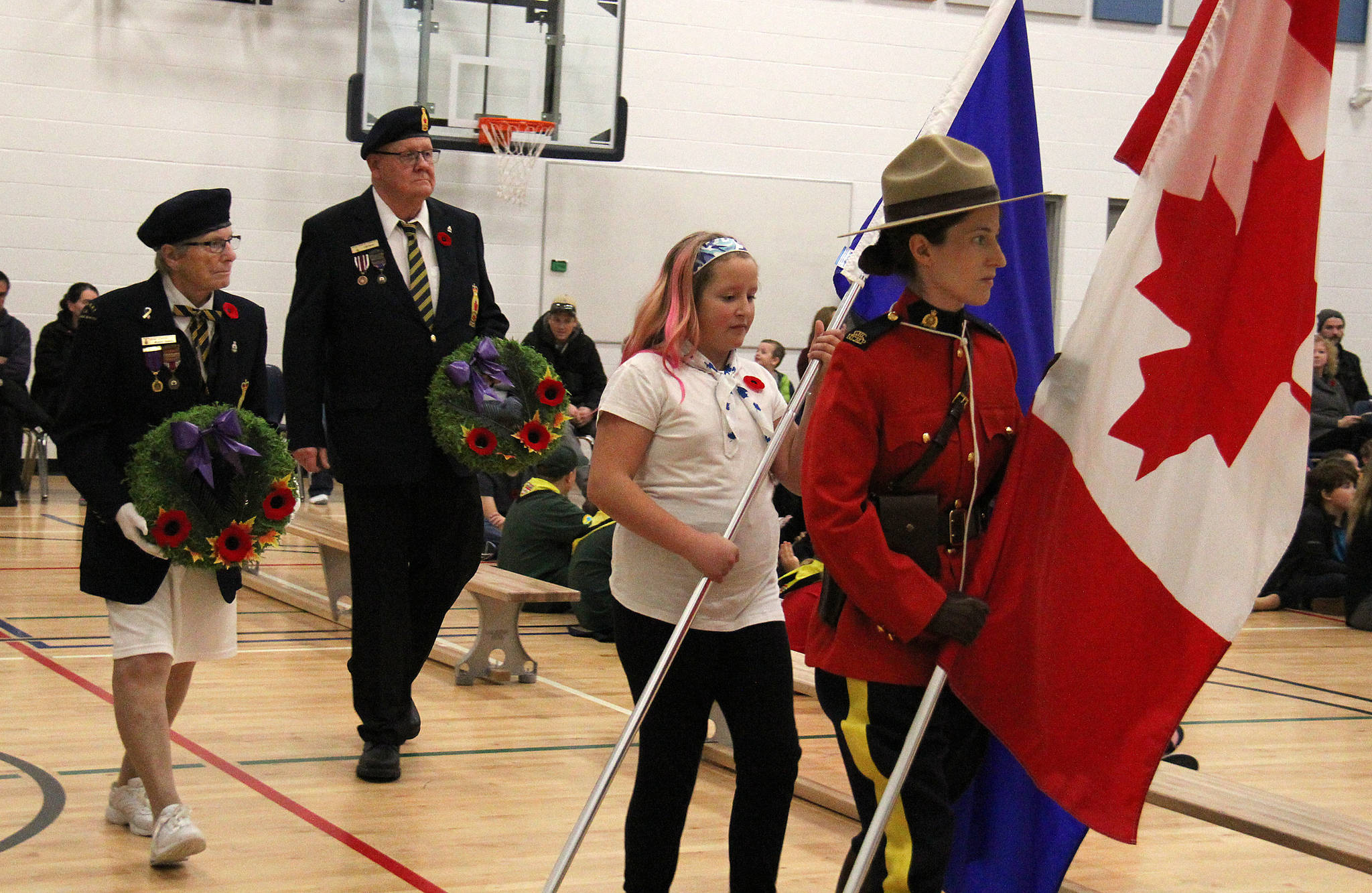Avery Fitch carries the Alberta flag at he beginning of Beacon Hill's Remembrance Day assembly. She was joined by Cst. Tania Donaldson who carried the Canadian flag and members of the Sylvan Lake Legion.